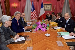 U.S. Secretary of State John Kerry - flanked by Under Secretary of State for Political Affairs Wendy Sherman and National Security Council Senior Director for Iran, Iraq, Syria and the Gulf States Robert Malley - sits across from French Foreign Minister Laurent Fabius and his advisers on March 25, 2015, in Lausanne, Switzerland, as the P5+1 allies discuss negotiations about the future of Iran's nuclear program. [State Department Photo / Public Domain]