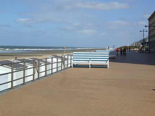 view of benches, white cabins and beach in Westende