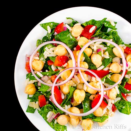 Chickpea, Rice, and Spinach Salad on plate with red onion garnish