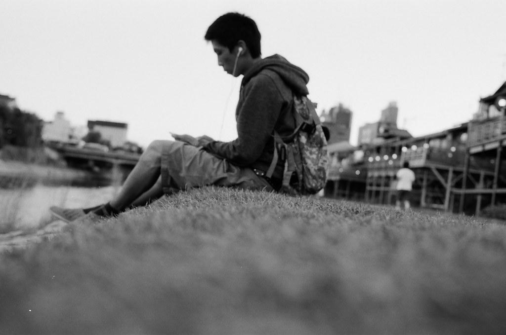 京都 Kyoto, Japan / Kodak TMAX / Nikon FM2 自己帶著買的布丁到鴨川河畔旁,我很假掰的把相機拿遠一點的地方自拍自己。  為自己唱了生日快樂歌,雖然那時候還在期待可能會等到一則關於來在她的祝福,但後來的確並沒有發生。  我記得 2014 年的生日是在福岡過的,2015 年在京都,那 2016 年呢?應該也要順著這習慣就到日本去吧。  下次還想再去一次京都,那裡真的還不錯待很多天。  Nikon FM2 Nikon AI AF Nikkor 35mm F/2D Kodak 100 TMAX Professional ISO 100 1273-0023 2015/09/29 Photo by Toomore