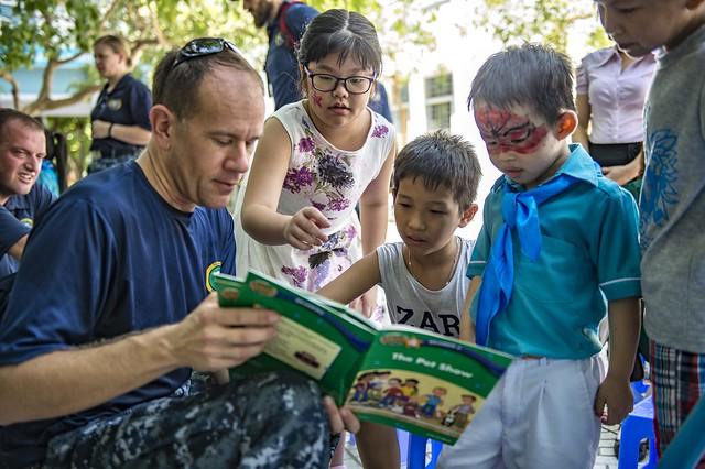 Cmdr. David Krause  reads to Vietnamese children.