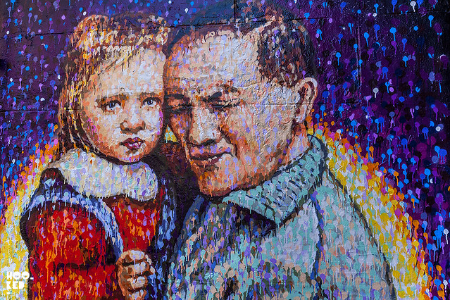 Brick Lane Street Art by JimmyC who paints a portrait of Joe's Kid cafe owner aged 3 with grandfather.