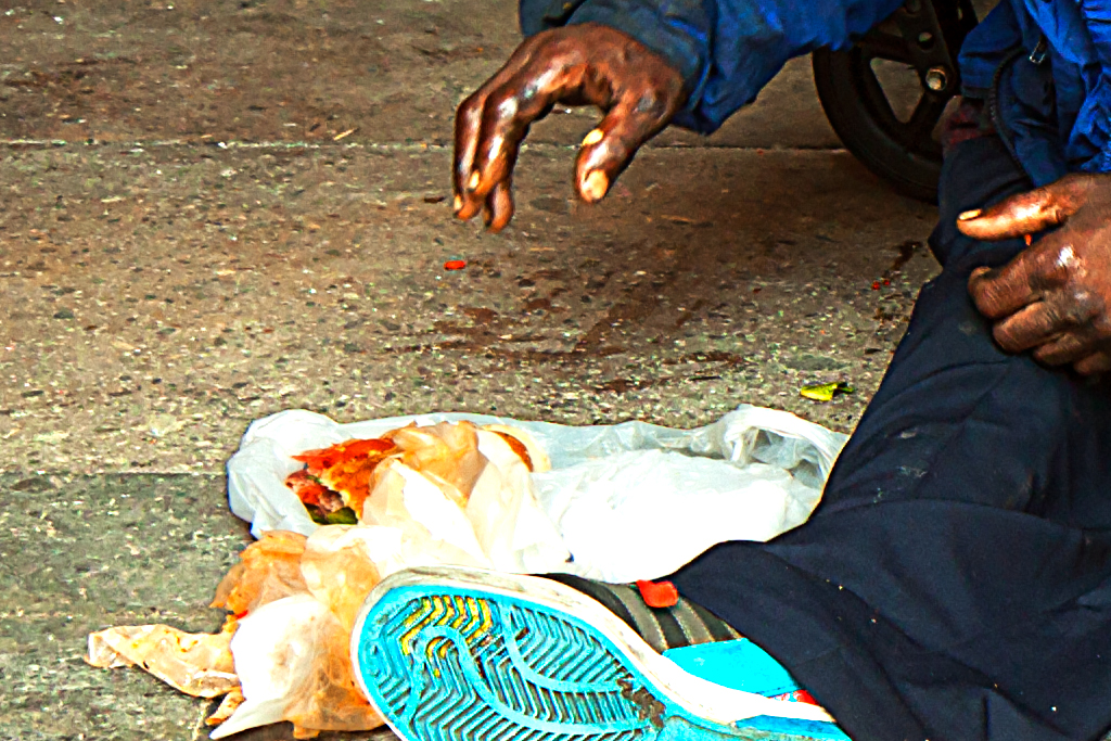 Man-sitting-on-ground-in-front-of-wheelchair-eating-hoagie--Center-City-(detail)