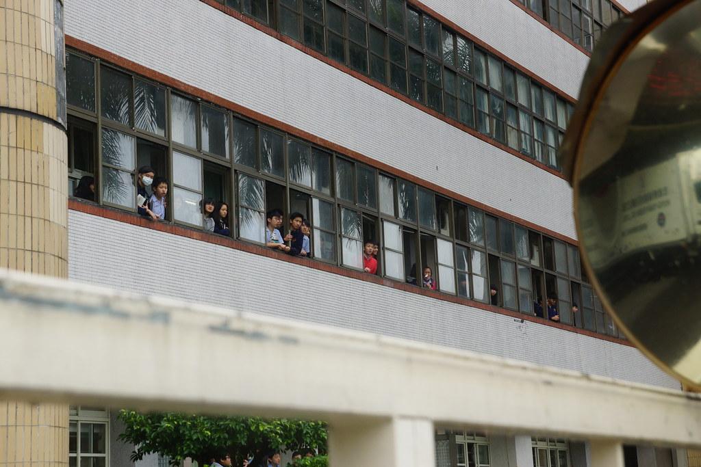 遊行隊伍行經中正國中,學生紛紛探頭向外觀望,甚至高呼支持。(攝影:王顥中)