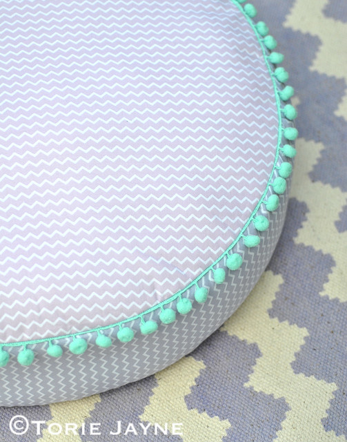 Round floor cushion with pom pom trim