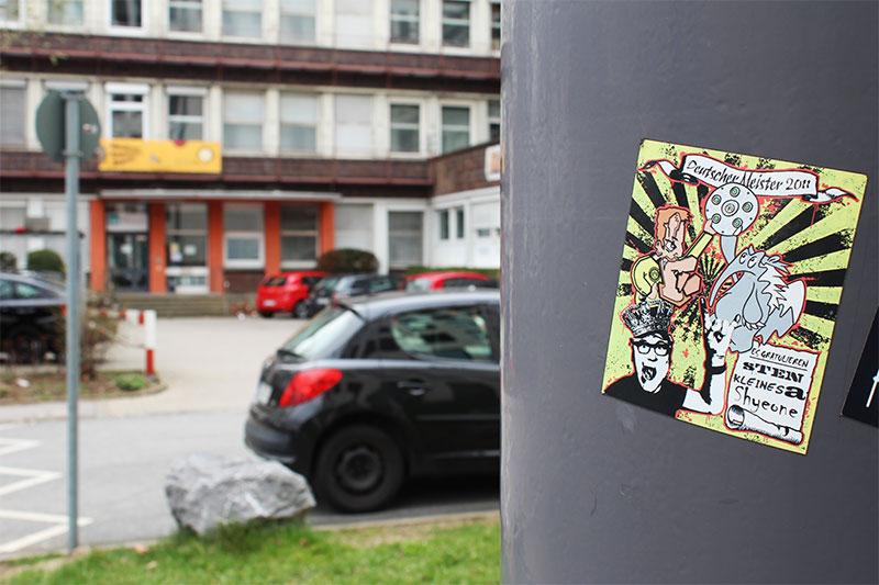 Sticker auf einem Laternenpfahl dahiner PKWs und ein Gebäude