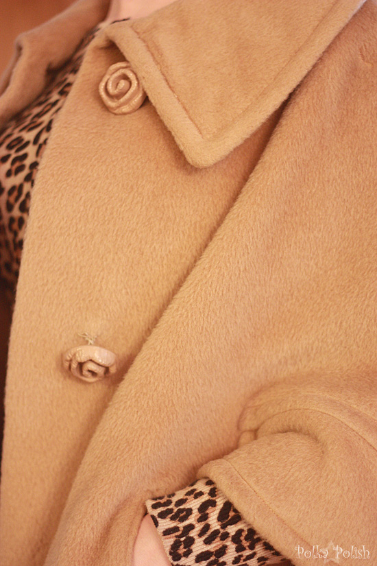Detail of the large rose-shaped buttons and slash pockets on the camel cape