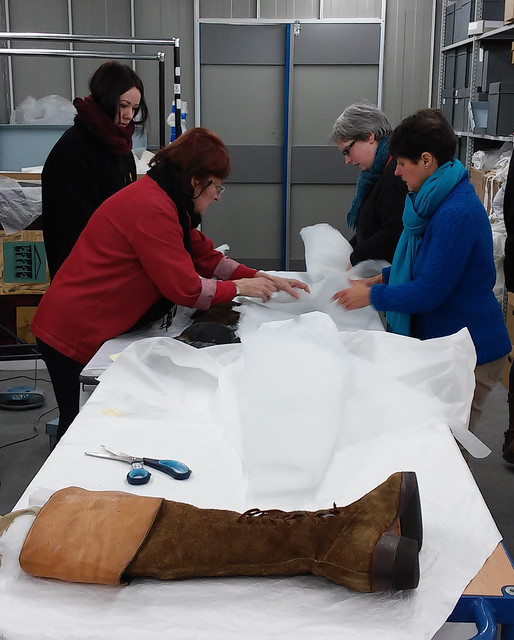 Staff working with costume conservator Judith Doré at the ROH Collections store, packing boots in preparation for the move to the new Costume Centre in Thurrock