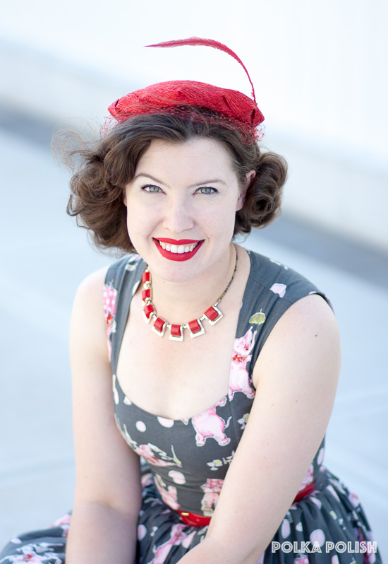A bright red 1950s hat with a single feather tops off this retro outfit.