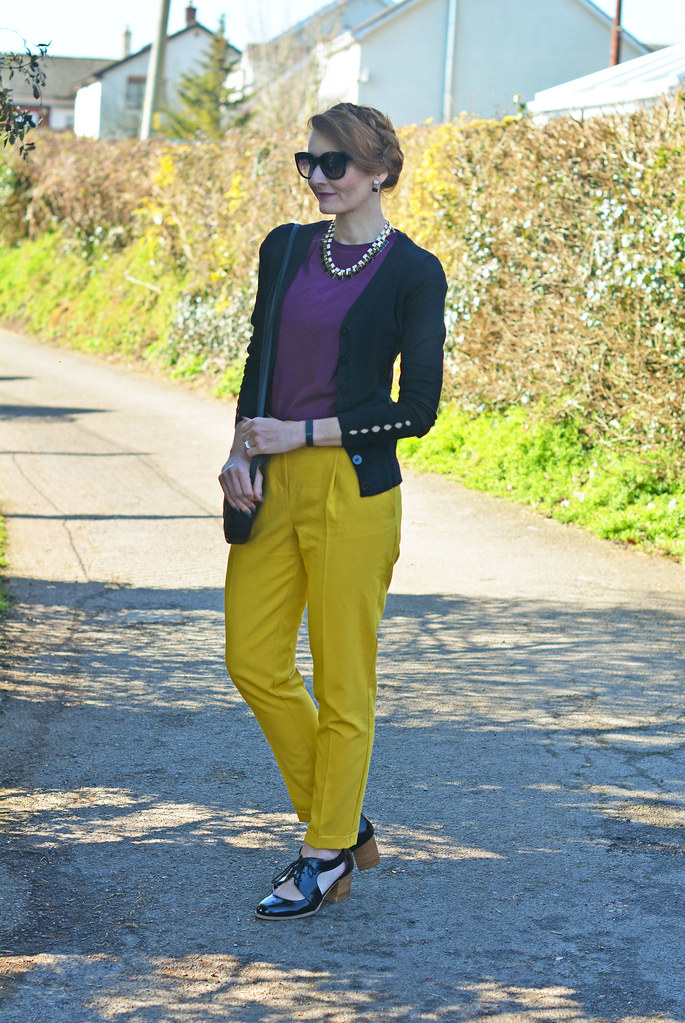 Purple t-shirt, mustard yellow trousers and black knit