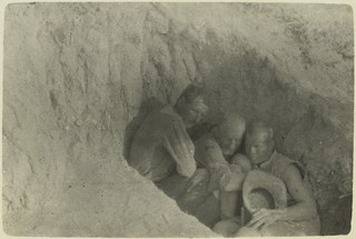 Sheltering from bursting shells, [showing three Anzac soldiers huddled together sheltering in a shallow trench, June? 1915] J.P. Campbell