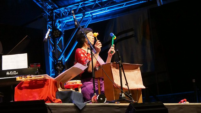 The photo shows Margaret Leng Tan kneeling at her toy piano and brandishing two children's toys (perhaps hammers or rattles), one with a smiley face on it.