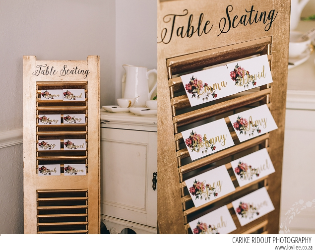 Wedding seating chart with Marsala wedding stationary on a gold shutter