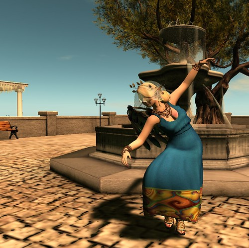 Blond woman in blue dress dancing in front of a fountain in a stone city square.