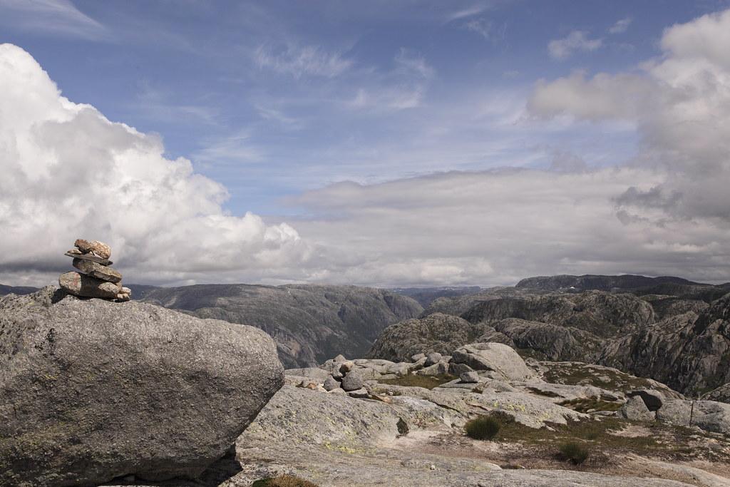 """Kjerag, Lysefjorden Kjerag er et bjergplateau på sydsiden af Lysefjorden, Ryfylke i Rogaland fylke i Norge. I den vestlige del af plateauet sidder Kjeragbolten, en 5 m³ stor sten, kilet fast i en kløft i fjeldet 1.000 m over Lysefjorden.  Stedet er et kendt turistmål i regionen. I 2006 havde Kjerag/Øygardstølen 27.375 besøgende. Turstien til Kjerag starter ved Øygardstølen – en restaurant 640 m over Lysebotn. Ved normal gang tager turen omkring to timer hver vej, af en kuperet og stejl vej, én vei. Fra 2008 er der tilbud om guiding ind til Kjerag i sommersæsonen.  Kjeragplateauet er et yndet udspringspunkt for BASE jumping. Flere stunts bliver også udført på eller ved plateauet. I august 2006 gik Christian Schau på slackline 1.000 meter over Lysefjorden. Da stuntet blev udført var det verdens højeste slackline.   I Kjeragfjeldet kan det på et bestemt sted i nærheden af toppen høres skudlignende smeld, samtidig med at en røg står ud fra bjergvæggen – det såkalte Kjeragsmellet. Efter hvad ældre folk fortæller, viser dette naturfænomen sig særlig i østenvind når vinden har en bestemt styrke. Hvad det kommer af er usikkert, men bygdefolk har fra tidligere tider ment at det er vand som bliver presset ud fraå fjeldvæggen. En opmålingsingeniør oplevede fænomenet i 1855. Han fortalte: """"Jeg hørte først enkelte skrald som efterhånden blev hyppigere og stærkere, derpå hørte jeg en overordentlig bragen og så en lysstråle fare i horisontal retning ud fra klippen indtil omtrent midten af fjorden hvor den opløste sig og forsvandt. Strålen var hvid og stærk. Først var den smal, og så blev den bredere, så smallere igen og derefter bred på ny til den opløste sig. Kilde: da.wikipedia.org/wiki/Kjerag"""