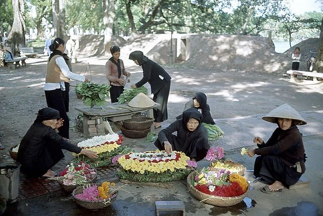 HANOI 1965 - Những bà cụ bán vòng hoa tang và rau bên bờ hồ Gươm - Photo by Romano Cagnoni