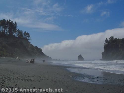Three hikers walk through the mist on Ruby Beach, Olympic National Park, Washington
