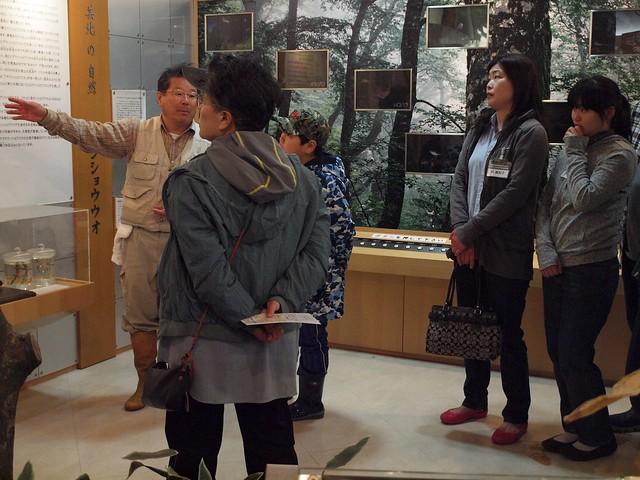 自然館の中で、サンショウウオについて説明する内藤先生と、真剣に聞き入る参加者さんたち。