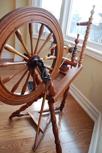 Rear view of antique flax spinning wheel with water dish depression