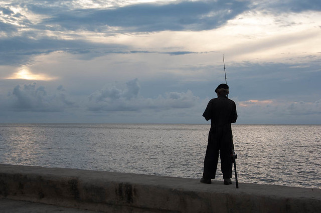 HAVANA/CUBA 25TH MAY 2006 - Fisherman standing on the Malecon at sunset