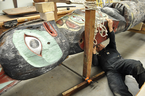 Tlingit Master Carver Wayne Price examines the Yax té (Big Dipper) totem located in a Forest Service workshop in Juneau. He is restoring the 74-year old totem. (U.S. Forest Service photo by Laurie Craig)