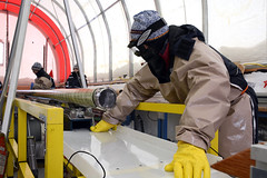 A science team member prepares to extract an ice core from the drill