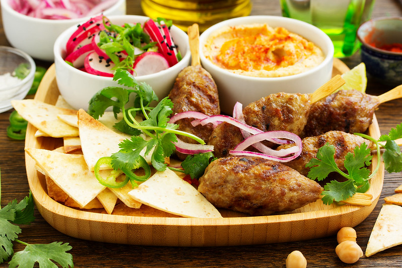 Kyufta (barbecue) of lamb with snacks (radish salad, chips and hummus.)