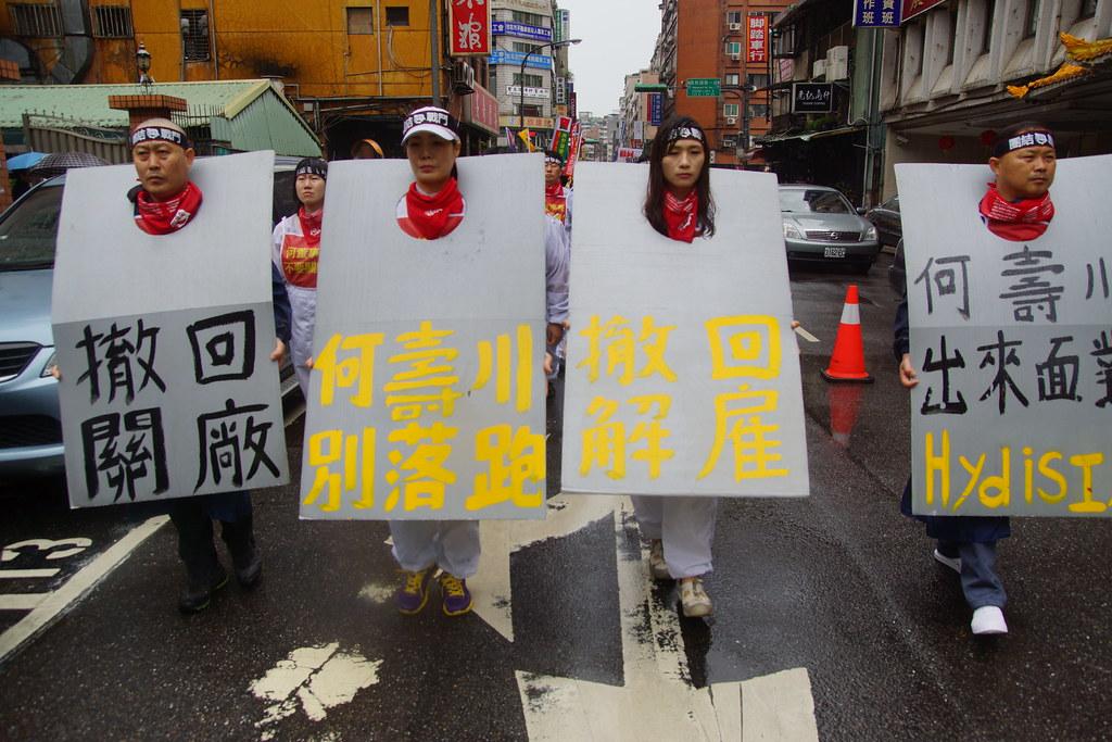 四位工人身戴寫有「撤回關廠」、「何壽川別落跑」、「撤回解僱」、「何壽川出來面對」等訴求立排。(攝影:王顥中)