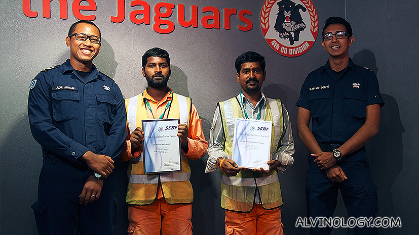Compulsory shot: Muthukumar and Shanmuganathan with the SCDF officers who assisted them. The two construction workers are holding their Public Spiritedness Awards.