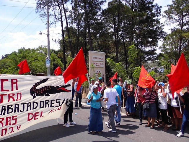 Workers gather to protest Lacoste's union busting activities, holding banners with the Lacoste logo