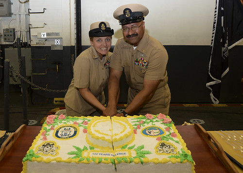 SAN DIEGO - Master Chief Ship's Serviceman Ioapo Puaatuua (right), the eldest master chief petty officer aboard amphibious assault ship USS Makin Island (LHD 8), and Chief Boatswain's Mate Danielle Rosetti, the command's youngest chief petty officer, participate in a ceremonious cake cutting in celebration of the Navy's 122nd anniversary since the establishment of the rank of chief petty officer.