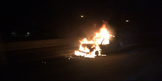 Picture of car on fire on side of road of the highway 101