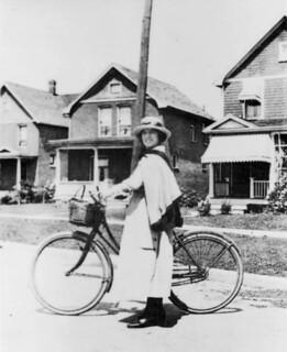 VON nurse standing with her bicycle / Une infirmière de l'Ordre de Victoria debout à côté de son vélo