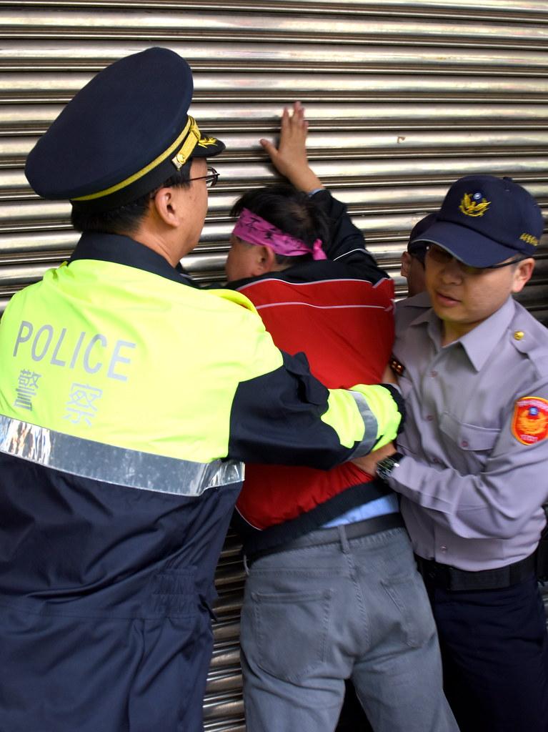 抗議者憤怒拍打立法院鐵門,遭警方架離。(攝影:宋小海)