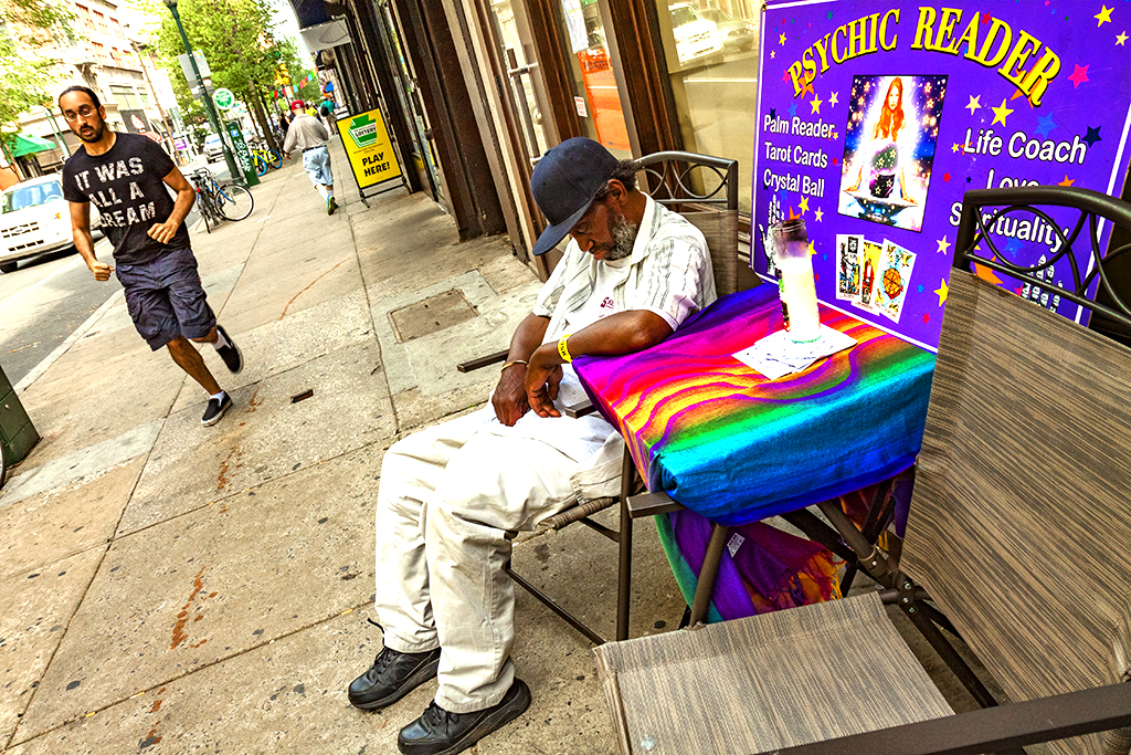 Homeless-man-sleeping-by-PSYCHIC-READER-sign--Center-City