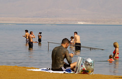 A young man covered in mud on Ein Bokek Beach, the Dead Sea, Israel