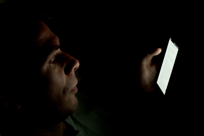 Person looking at smartphone in the dark