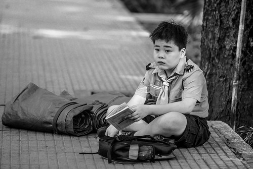 A boy scout sitting by the roadside.