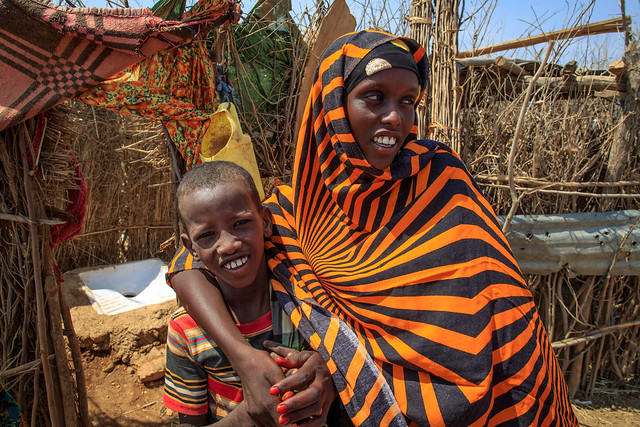 Fatuma Nuior, 16, and her cousin Audi Arab, 12, stand by her latrine next to her house in Ber'aano Woreda in Somali region of Ethiopia 12 February 2014. The village is the first village declared ODF (Open Defecation Free) and All but one household has a latrine. While flags fly over each latrine. In Somali Region water supply coverage is estimated at 59.7%, lower than the national average of 68.5%. The need for water supply normally increases in the dry season, especially at the time of drought such as in recent years. However, the technical and organizational capacity of the Somali Regional State Water Resources Development Bureau (SRWDB) the government agency responsible for water supply and facilities management in the region to satisfy the water supply need is not adequate to cope with the situation. Donor agencies and NGOs are making efforts to ameliorate the situation by constructing and repairing water supply facilities across the region, supplying water by water trucks during chronic shortages, but the supply is still significantly below the demand.