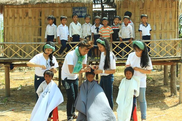 Các tinh nguyện viên cắt tóc cho trẻ em Raglay với sự hỗ trợ của các thợ cắt tóc chuyên nghiệp từ Salon Thế Giới Tóc