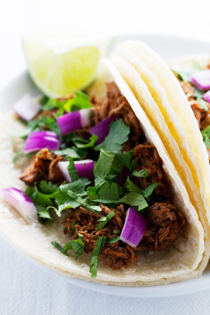 Slow cooked barbacoa beef that is just exploding with flavor! It's simple to make, requires no babysitting, and the meat is just fall-apart tender and delicious. Use this shredded beef on tacos, burritos, salads or anything else you please! #barbacoabeef #barbacoa #slowcooker #chipotle | Littlespicejar.com