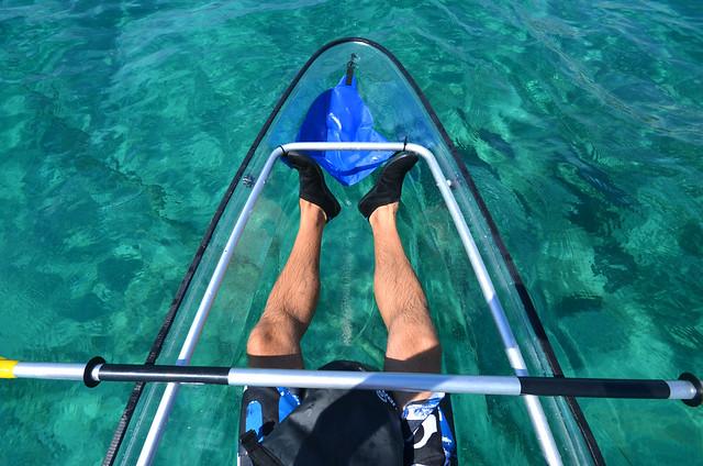 Mis pies visto desde arriba en el kayak transparente de alquiler en Menorca