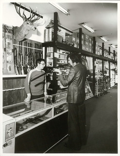 A customer looking at a shotgun at a sports shop in Wellington, (Mel Lewis Sports), Lambton Quay