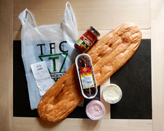 Groceries laid out on a table on top of a TFC-branded carrier bag: an oval package of dates, a jar of red chilli paste, small round tubs of hummous and taramasalata, and a long and narrow oval flatbread.