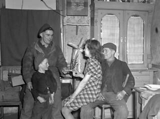 Lance-Corporal Harry Repay of the Scout Platoon, South Saskatchewan Regiment, visiting a Dutch family... / Le caporal suppléant Harry Repay, du peloton d'éclaireurs du régiment South Saskatchewan, chez une famille hollandaise...