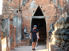 Tourist and a Row of Broken Buddhas