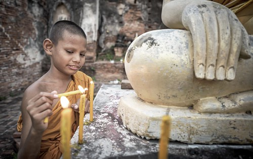 Novice Monk fire candles to the Buddha