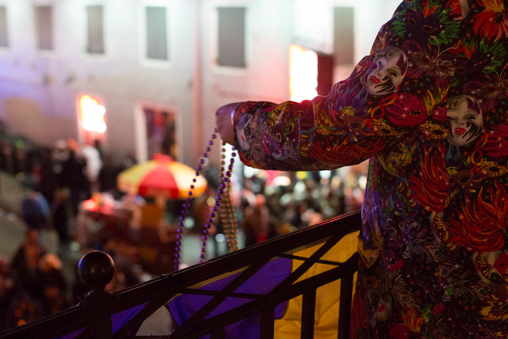 Throwing beads from Bourbon Street Balcony