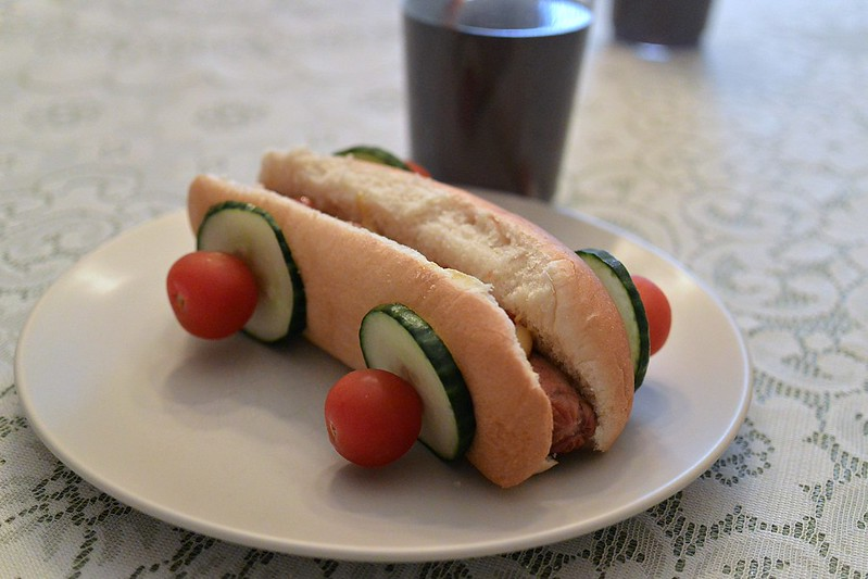 Race Car Hot Dogs with cucumbers and cherry tomatoes as wheels