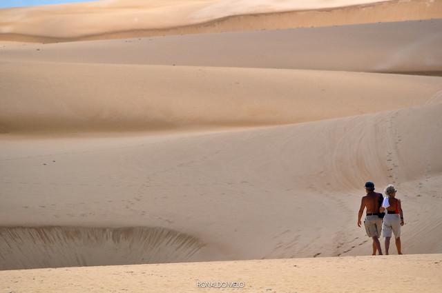 An older man and older woman walking in the dunes of Lencois Maranhenses National Park, Brazil